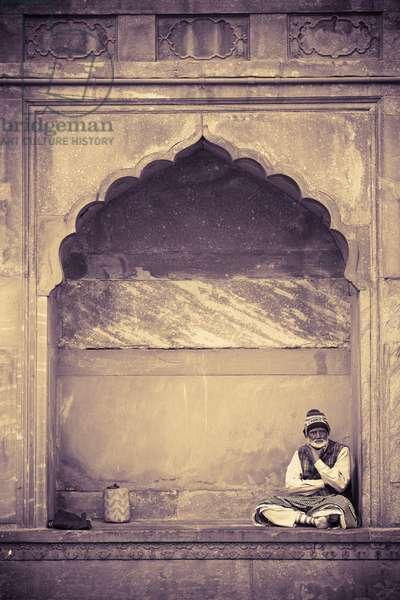 Man sitting Under Architectural Arch, Delhi, India (photo)