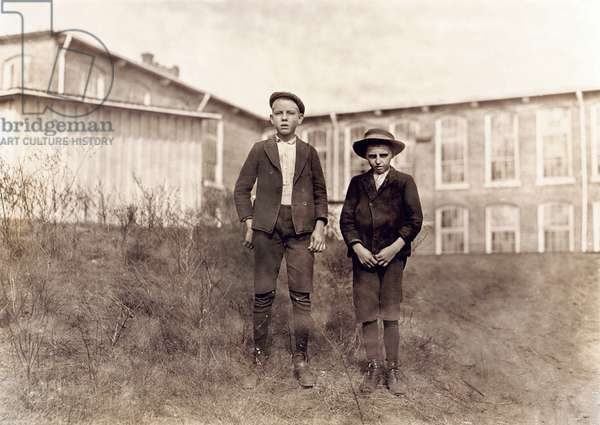 Arthur Shelly (left), 14 years old and Tommy Ashville, about 11 years old, Textile Mill Workers, Full-Length Portrait, Chester, South Carolina, USA,  November 1908 (b/w photo)