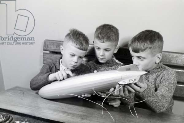 Three school boys are curiously examining a zeppelin model that has a swastika painted on its elevator, zeppelin village near Frankfurt am Main, Germany 1930s (b/w photo)