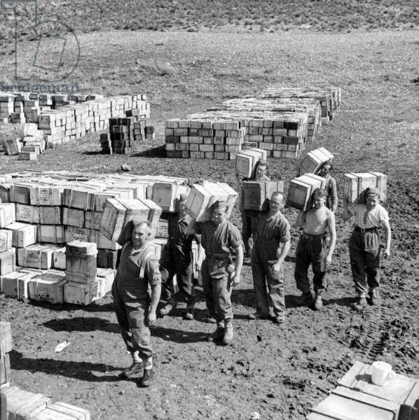 A compo ration dump and men carrying more supplies to it, March 1943 (lantern slide)