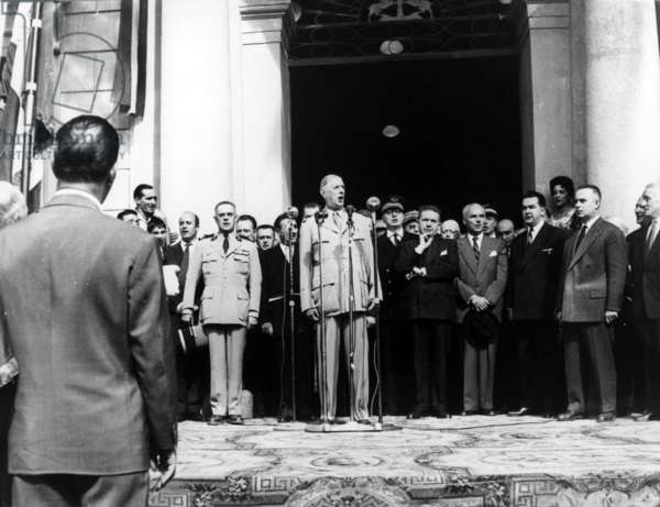 General de Gaulle singing La Marseillaise at the Hotel de Ville, on his right, Colonel de Bonneval, Aide de Camp, and on his left, with his hat in his hands, Pierre Guillaumat, Minister of the Armies, 3-4 October 1958 (b/w photo)
