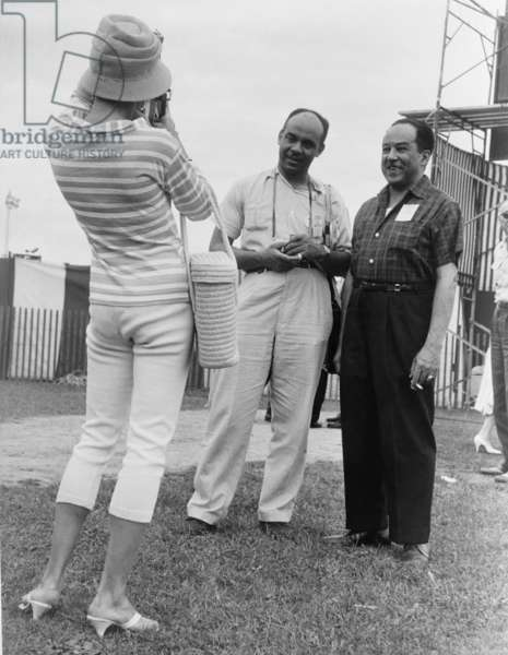 Ralph Ellison and Langston Hughes, famous African American authors, pose for an admirer's photo at the Newport Jazz Festival. c. 1959