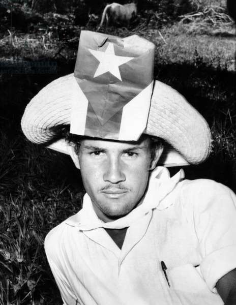Cuban Patriot wearing a flag decorated hat. He is a farmer from the hill country who has traveled to Havana for the celebration of the sixth anniversary of the '26th of July Movement' that brought Fidel Castro to power. July 23, 1959