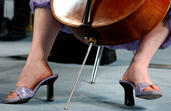 Feet of female cellist and the endpin of cello
