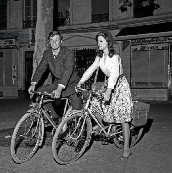Jean-Paul Belmondo and Marie Versini on a bike on the set of the film
