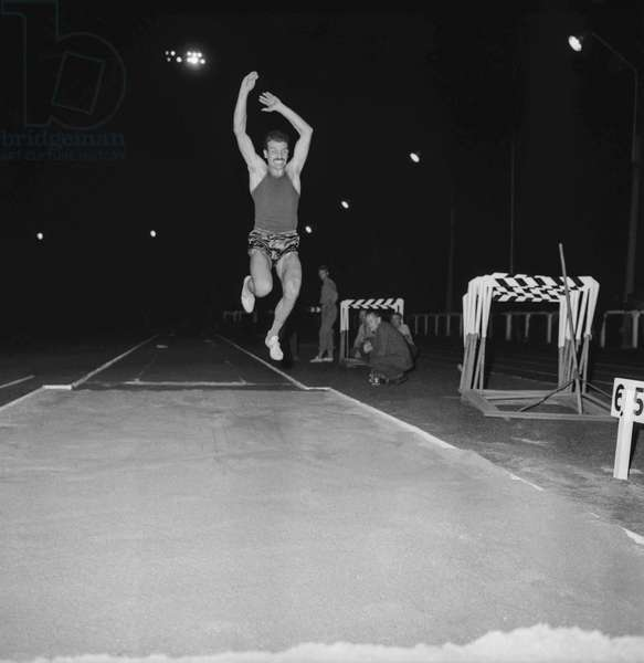 Before the Olympic Games, an athletism meeting at La Croix de Berny, August 20, 1960 : long jump with Christian Collardot (b/w photo)