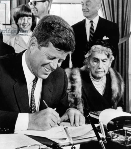 President John Kennedy signs a Joint Resolution for the Woodrow Wilson Memorial Commission. Looking on is 89 year old Edith Bolling Galt Wilson. Behind the President is Jessie Sayre, 12, great granddaughter of the Wilson. Oct. 4, 1961