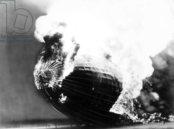 The Hindenburg disaster. People run away from the burning dirigible, dwarfed by its huge scale. May 6, 1937.