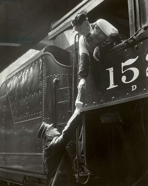 Train conductor giving paper to train engineer (b/w photo)