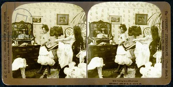 Stereoscopic card depicting a woman being laced into a corset, c.1900 (sepia photo) (see also 473244)