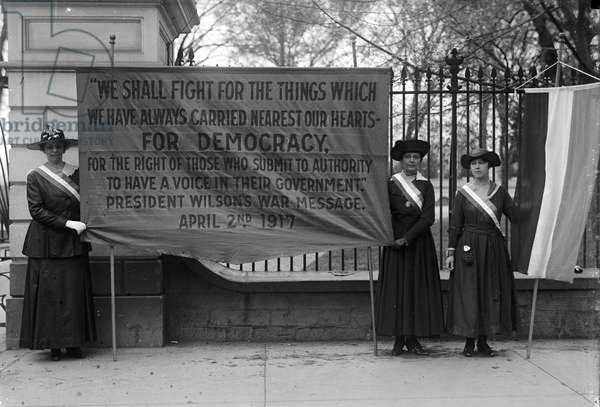 WHITE HOUSE: SUFFRAGETTES Women suffragettes holding a banner addressing President Woodrow Wilson, in front of the White House, Washington, D.C., 1917.