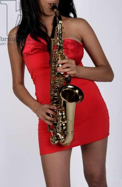 Female playing an alto saxophone