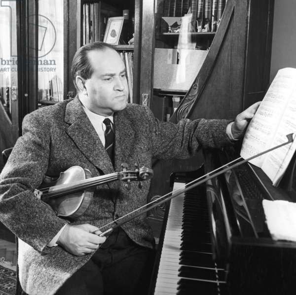 David Oistrakh, violinist, conductor, professor and head of the violin department at Moscow State Tchaikovsky Conservatory, at home, 1958 (b/w photo)