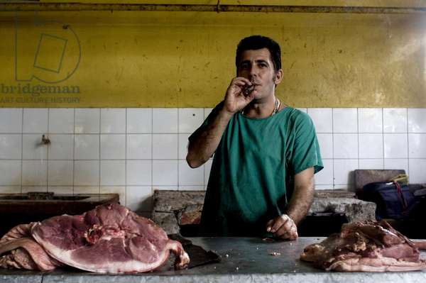 A man smoking cigar at his butchery. Havana City, 50th Anniversary of the Socialist Revolution. Fifty years since the fall of the Batista government. So began the Socialist Revolutionary State, under the troops of Fidel Castro, Che Guevara and Camilo Cienfuegos. In 2009, while the Cuban society remains in constant adaptation and after the Regime entered into a new social and economic post-Sovietic period, Cuba reflects the need of present day revolutionary changes. Havana, Cuba. February 28, 2008.  (photo)