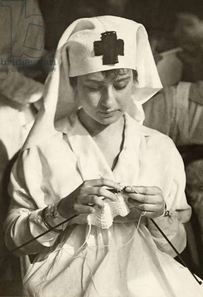 A World War I era American Red Cross nurse knitting, 1917 (b/w photo)