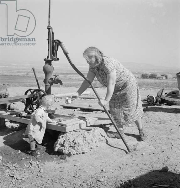 Mrs. Soper with youngest child at the well in Malheur County, Oregon, 1939 (b/w photo)
