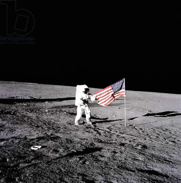 "Apollo 12 Astronaut Charles ""Pete"" Conrad stands beside the United States flag after is was unfurled on the lunar surface during the first extravehicular activity (EVA-1), on November 19, 1969"