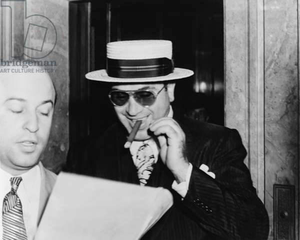 Al Capone, with a cigar and a big smile, leaving Federal building in Miami, Florida, preceded by his attorney Abe Teitelbaum. 1941