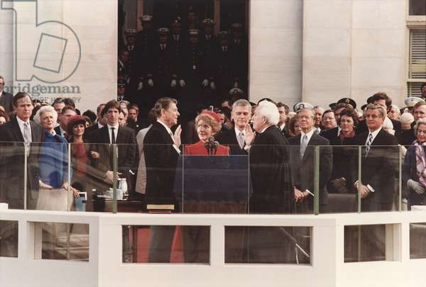 President Reagan being sworn in on Inaugural Day U.S. Capitol. Chief Justice Warren Berger leads the ceremony as Nancy Reagan holds the Bible. On left are the VP George Bush Ron Reagan and his wife. On right is the outgoing Democrats Jimmy Carter and VP. PO-USP-INAUG-Reagan_NA-12-0104M