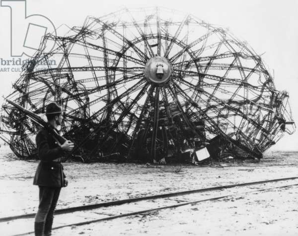 Hindenburg wreckage guarded by a soldier at the Naval Air Station in Lakehurst, NJ. May 1937. The German passenger airship's twisted metal skeleton remains