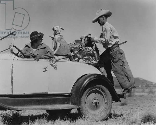 Itinerant cowpuncher travels about with saddles, dog and wife from ranch to ranch seeking work, Alpine, Texas, USA, 1938 (b/w photo)