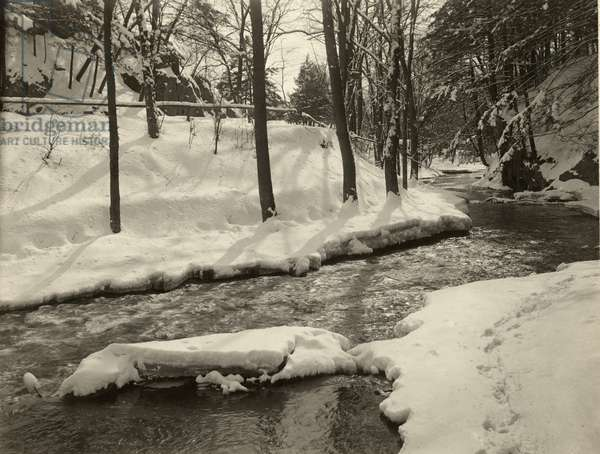 A fast moving stream meanders through a snow covered woodland, USA, 1916 (b/w photo)