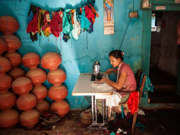 A woman works at her sewing machine in the village of Napa where Mahatma Ghandi passed through during his Salt March (photo)