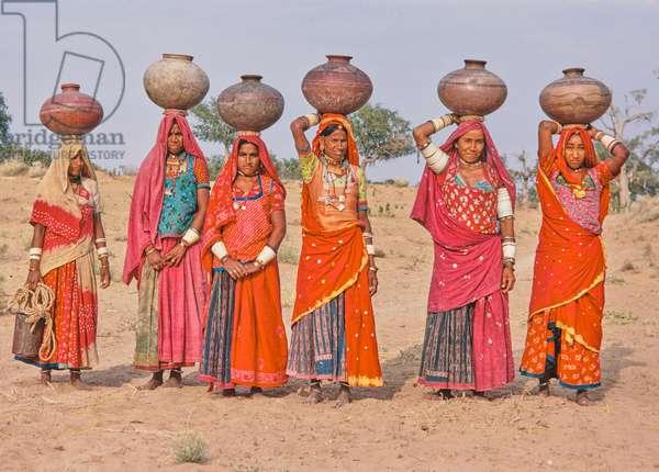 Village women carrying pots on heads, rural scene, Thar Desert, Rajasthan, India (photo)
