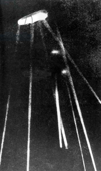 German Zeppelin lit up by searchlights (b/w photo)
