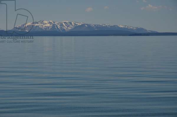 The calm waters of Yellowstone Lake and a snow topped mountain peak in the background in Yellowstone  National Park, Wyoming  (photo)