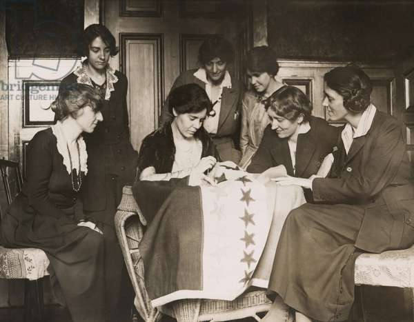 National Woman's Party activists watch Alice Paul sew a star onto the NWP Ratification Flag, representing another state's ratification of the 19th Amendment. Party members, Mabel Vernon is seated far left), and Anita Pollitzer is standing on right. c. 1919