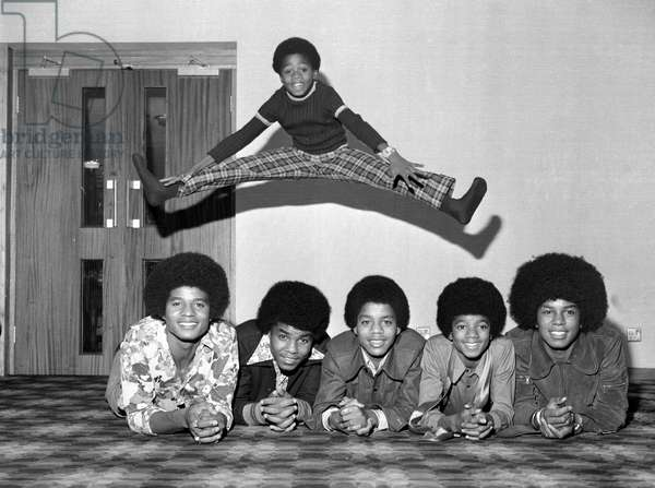 Members of the Jackson Five pop group become the Jackson Six when the latest addition to the family Randy Jackson joined the group, the group pictured left to right are: Jackie, tito, Marlon, Michael, Jermaine and little Randy jumping above all the lads, November 1972 (b/w photo)