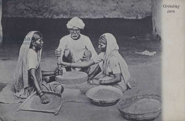 Man and women grinding corn, North Africa (b/w photo)