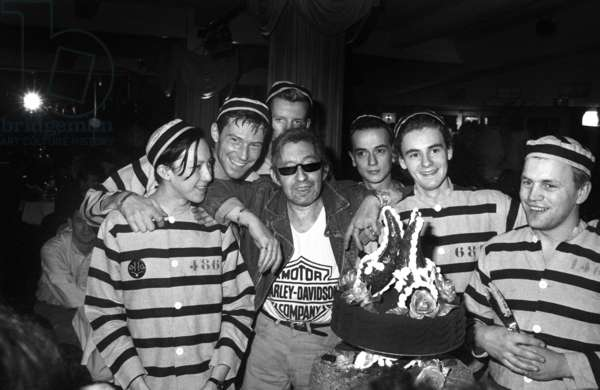 French Singer Serge Gainsbourg celebrating his birthday at the Palace with waiters dressed as prisoners, Paris, 22 March 1988 (photo)