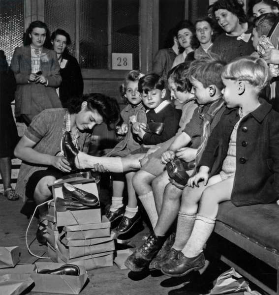 Distribution of Shoes To Children of Prisoners Interned in A Concentration Camp By Federation of Leather in 1945 in Paris (b/w photo)