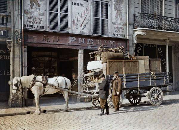 A horse cart is loaded with furniture and personal belongings in front of a leather goods shop, Reims, France, May 4, 1917 (autochrome)