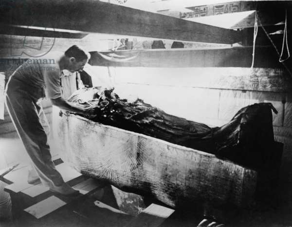 Howard Carter (1874-1939), turning back a shroud covering the inner coffin of Tutankhamen. March 1926