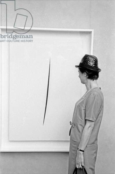 A woman observing a Concetto Spaziale by Lucio Fontana at the 32nd Art Biennale, Venezia, Italy
