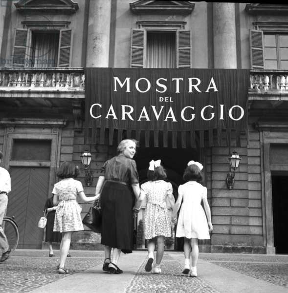 A grandmother accompanies three girls to the Caravaggio Exhibition at Palazzo Reale, Milan, Italy, May 1950 (b/w photo)