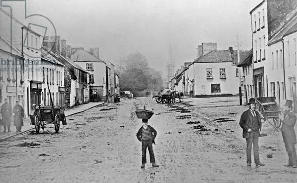 A young delivery boy stands nonchalantly in the main street of Clonmorris, County Mayo, Ireland, 1871 (albumen print)