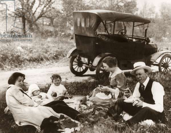 FAMILY PICNIC, c.1918 A family having a picnic on the side of a road, with a Model T Ford in the background. Photograph, c.1918.