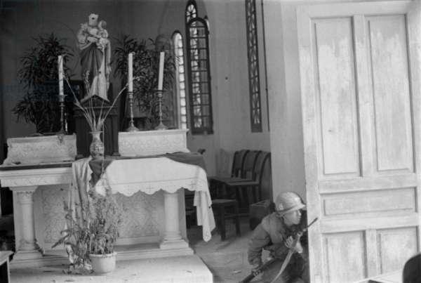 Vietnam War-Tet Offensive. US Marine crouches behind a church door during the Battle of Hue. Feb. 9, 1968
