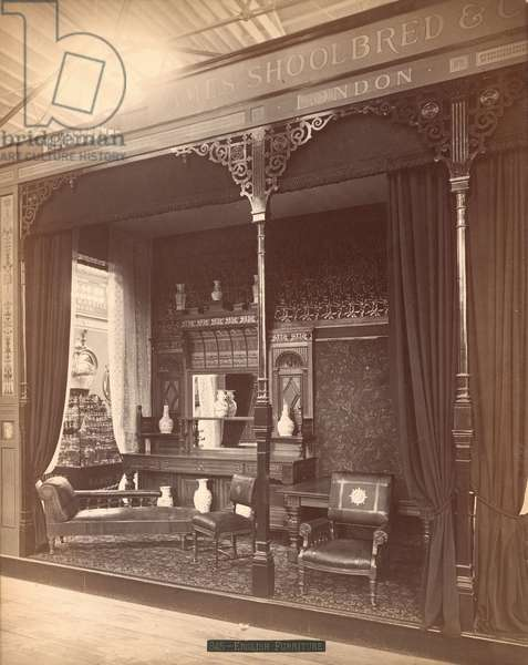 James Shoolbred & Co.'s exhibit -- Main Building, Parlor scene consisting of a sideboard and mirror with vases on and in front, chairs, a table, and a couch. On the floor is a carpet and the walls are covered in floral wallpaper, 1876 (b/w photo)