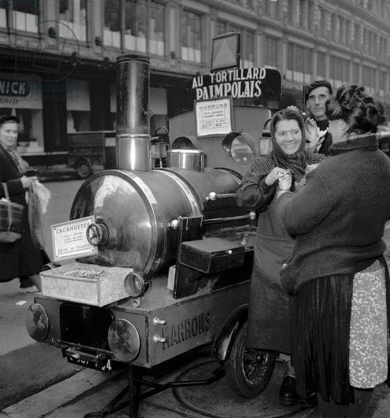Woman selling roasted chestnuts, December 16, 1949 (b/w photo)