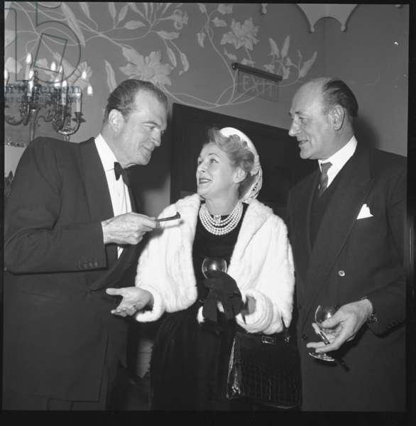 George Sanders with wife Benita Hume and friend, Quaglino's, London, UK, 1959