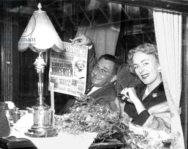 Christine Jorgensen and her manager with the London Playbill on a boat train, London, UK, 1954 (b/w photo)