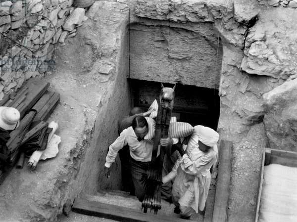Discovery of the tomb of pharaoh Tutankhamun in the Valley of the Kings (Egypt) : Howard Carter carries with an egyptian worker's help a statue composing the treasure