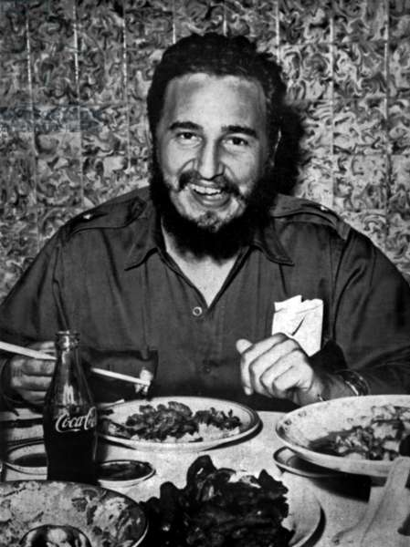 Fidel castro, head of cuban state, eating a chinese meal with chopsticks and drinking Coca Cola, c. 1960