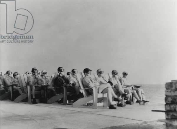 VIPs view the DOG shot, an 81 kiloton atomic detonation wearing safety goggles. They are sitting on Adirondack chair of the Officers Beach Club patio on Enewetak Island. The blast wave arrived at the location of the VIPs some 45 seconds after the initially silent flash. April 7, 1951. It was first test in a series, Operation Greenhouse, that tested principles leading to developing thermonuclear weapons (hydrogen bombs)