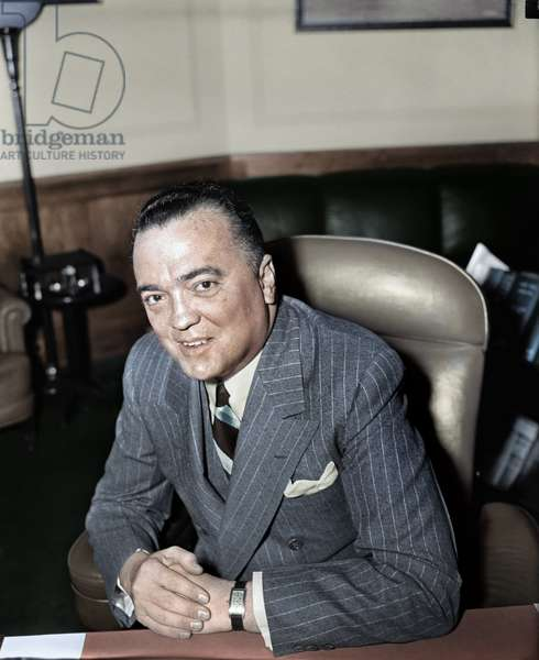 JOHN EDGAR HOOVER (1895-1972). American lawyer and public official. Photographed in his office as Director of the F.B.I., 5 April 1940, digitally coloured  by Granger, NYC